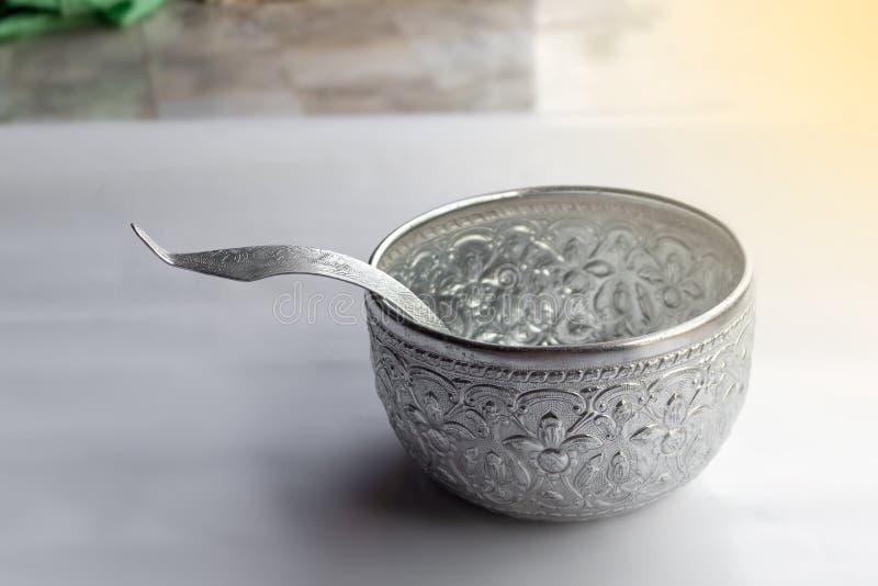 Cuenco del agua y plata tailandeses de la cucharón en el fondo blanco imagen de archivo libre de regalías