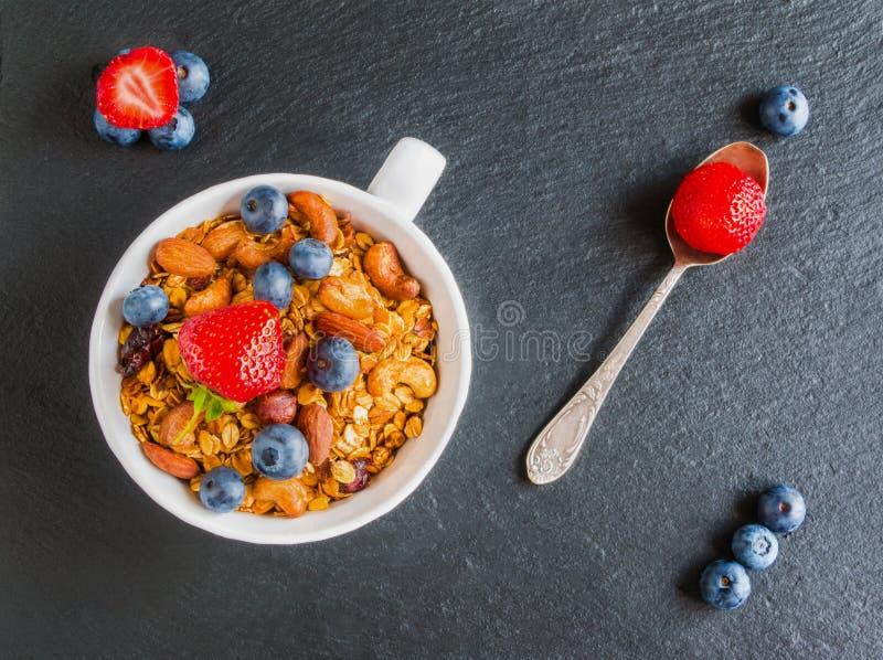 Cuenco del desayuno con el granola hecho de escamas de la avena, frutas y nueces secadas, y arándanos y fresas frescos fotografía de archivo
