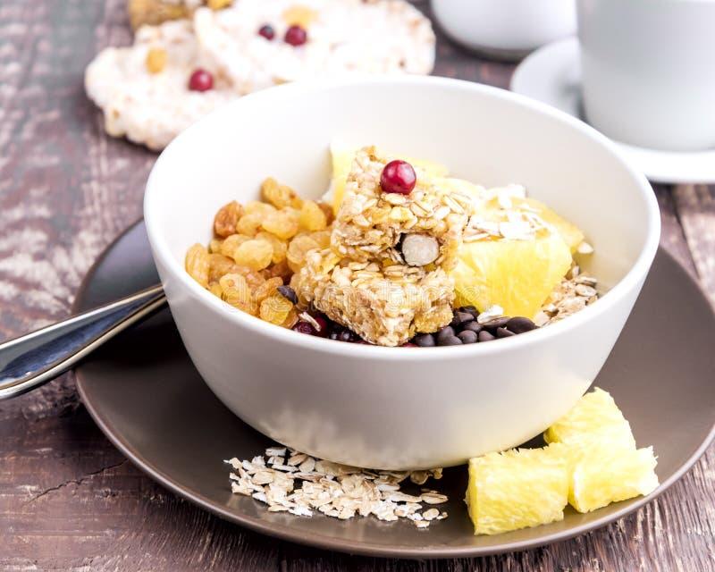 Cuenco del desayuno con las escamas Berry Raisins de la avena de Muesli y la naranja fotos de archivo libres de regalías