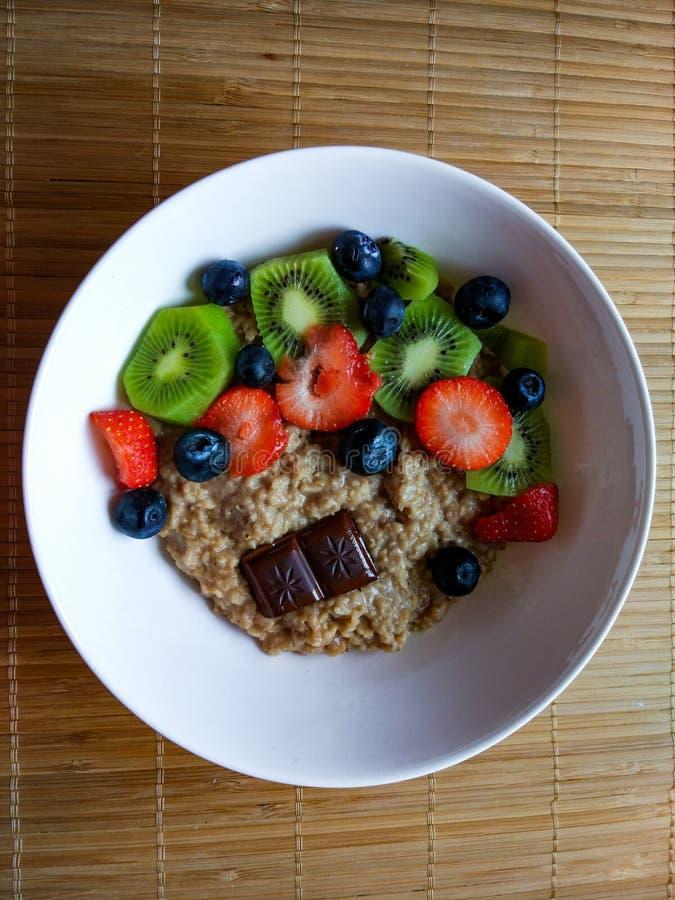 Cuenco del desayuno con las fresas, el kiwi, el arándano con muesli y el chocolate oscuro desde arriba foto de archivo libre de regalías