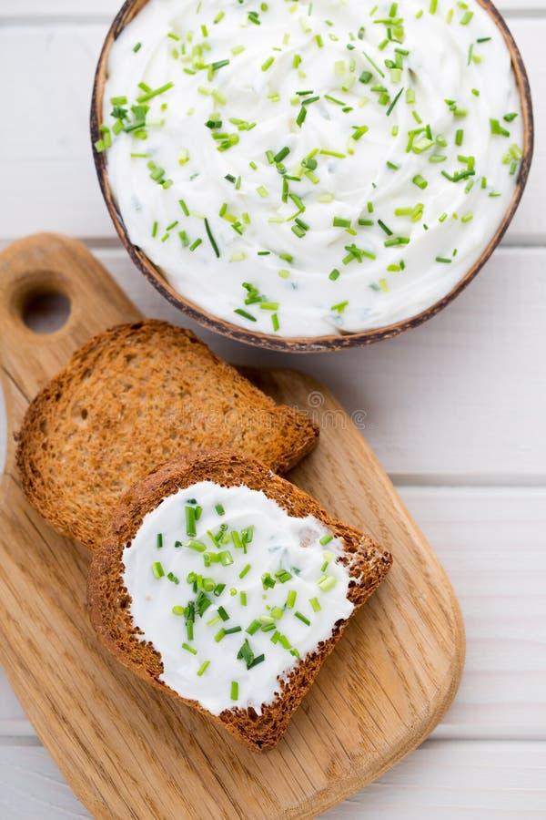 Cuenco del queso cremoso con las cebollas verdes, salsa de la inmersión en tabl de madera fotos de archivo