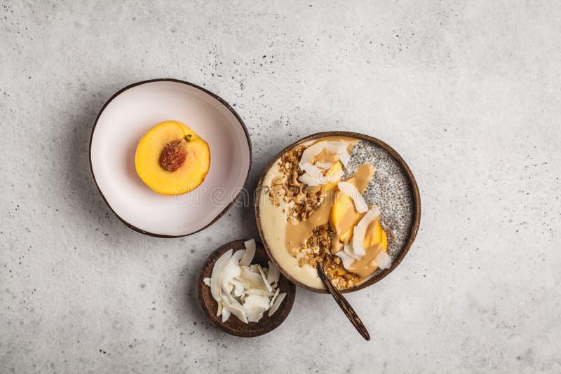Cuenco del Smoothie con el pudín, el melocotón, el coco y el granola del chia en a foto de archivo