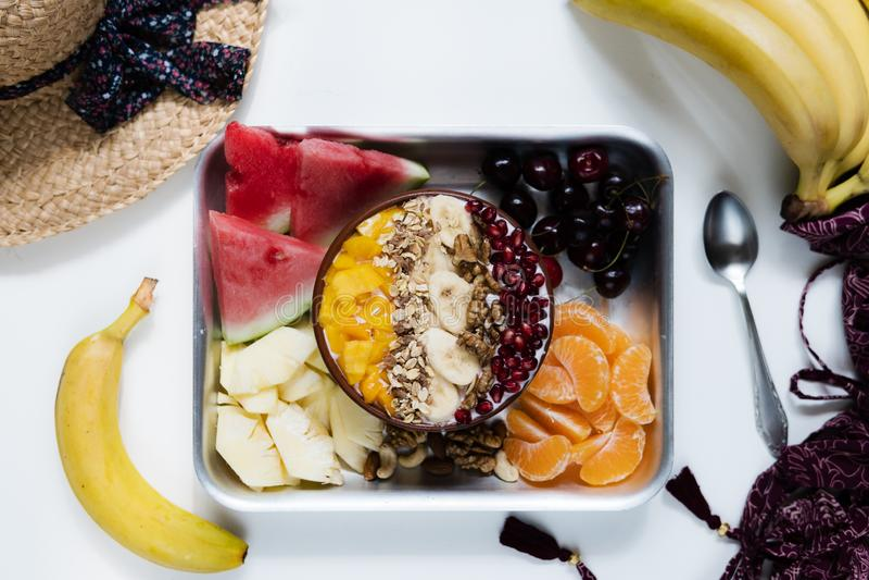 Cuenco del Smoothie con las frutas tropicales coloridas en la bandeja de la porci?n, visi?n superior desde arriba foto de archivo
