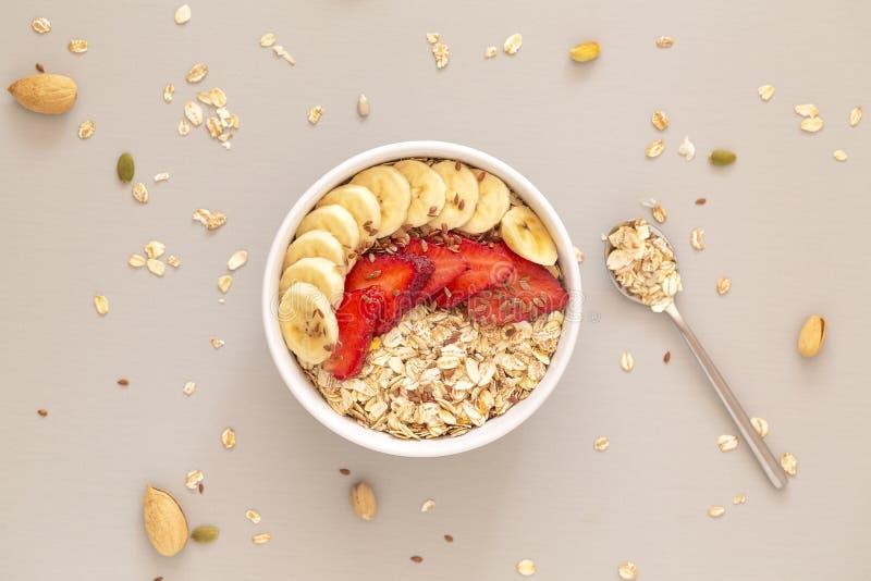 Cuenco del Smoothie con muesli, las fresas, las rebanadas del pl?tano y la semilla de lino Concepto sano del alimento Endecha pla imagen de archivo