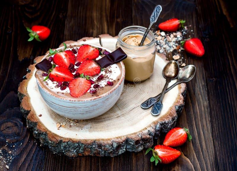 Cuenco del smoothie del maca de la mantequilla de la almendra del chocolate rematado con las fresas cortadas, el chocolate tajado fotos de archivo