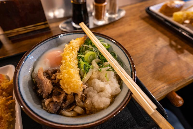 Cuenco delicioso de tallarines japoneses de los ramen con la verdura, el huevo, la carne de vaca y el tempura con los palillos en fotos de archivo libres de regalías