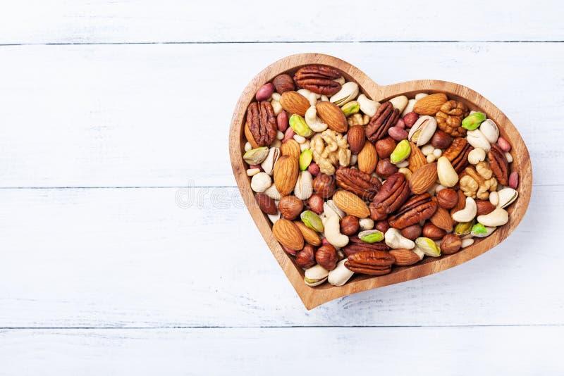 Cuenco en forma de corazón con las nueces mezcladas en la opinión de sobremesa de madera blanca Comida y bocado sanos fotos de archivo