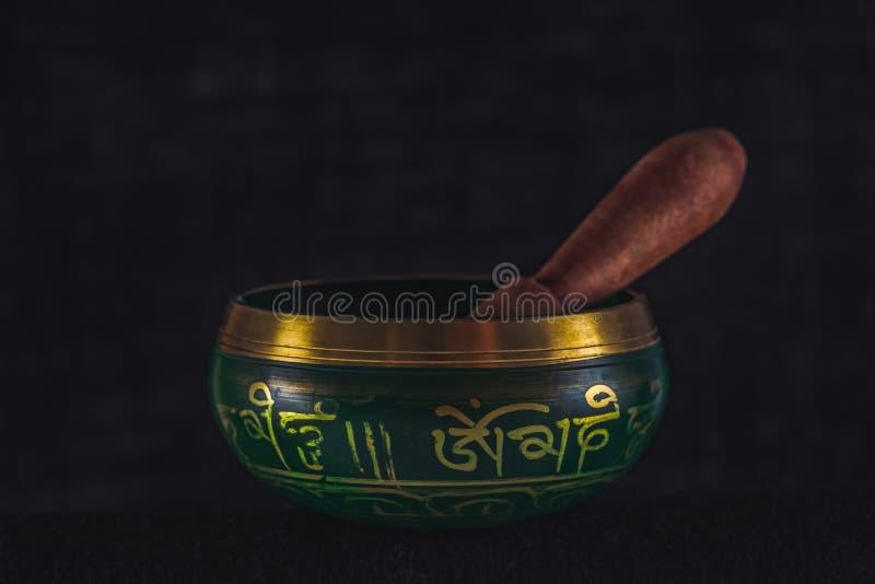 Cuenco hecho a mano tibetano del canto con el palillo, en un fondo oscuro imagen de archivo
