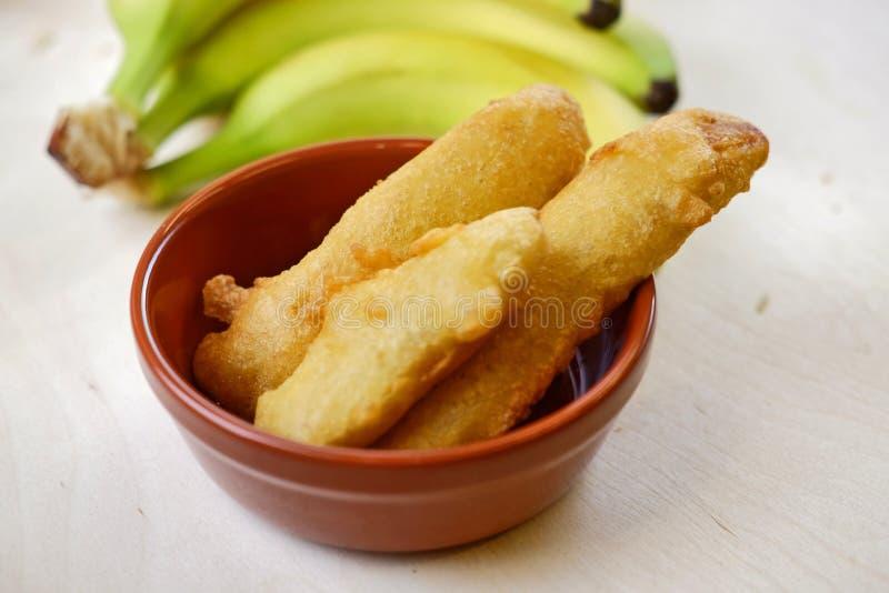 Cuenco indio tradicional de plátanos fritos con el manojo de plátanos frescos en el fondo fotografía de archivo