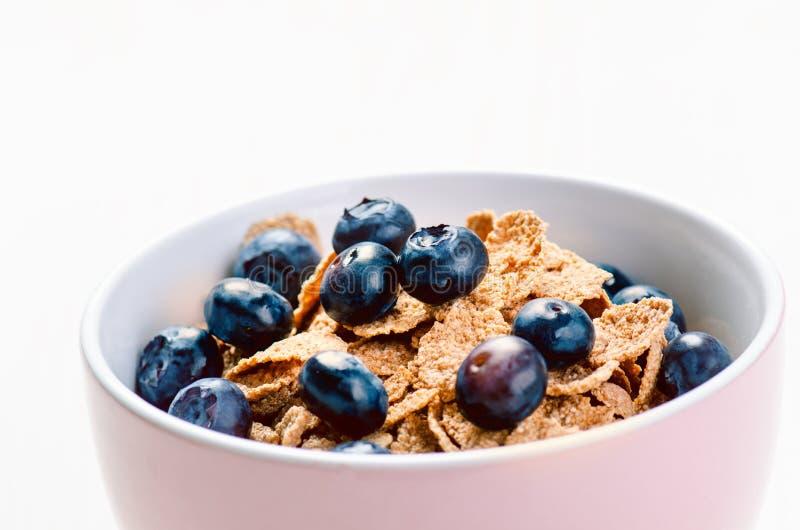 Cuenco lleno del muesli en una tabla blanca con el arándano Cereales de desayuno sanos con la leche, semilla, fruta Escamas de la fotografía de archivo