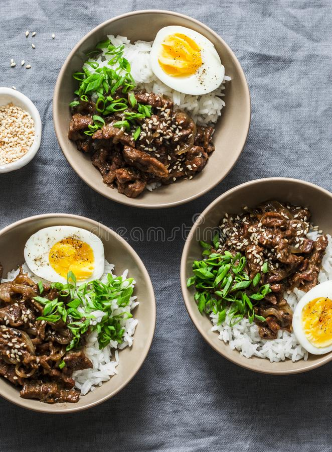 Cuenco picante de la carne de vaca, del arroz y del huevo hervido en el fondo gris, visión superior Concepto asiático del aliment imágenes de archivo libres de regalías