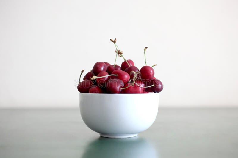 Cuenco por completo de cerezas maduras rojas con el espacio de la copia imagenes de archivo