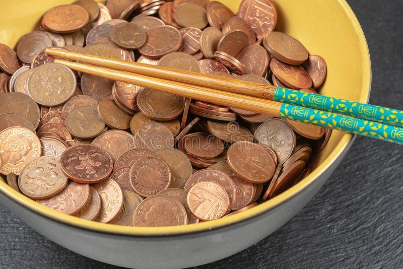 Cuenco por completo de monedas del esterlina y de los palillos Concepto imagenes de archivo