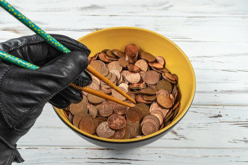 Cuenco por completo de monedas del esterlina y de una mano que sostienen los palillos Concepto imagenes de archivo