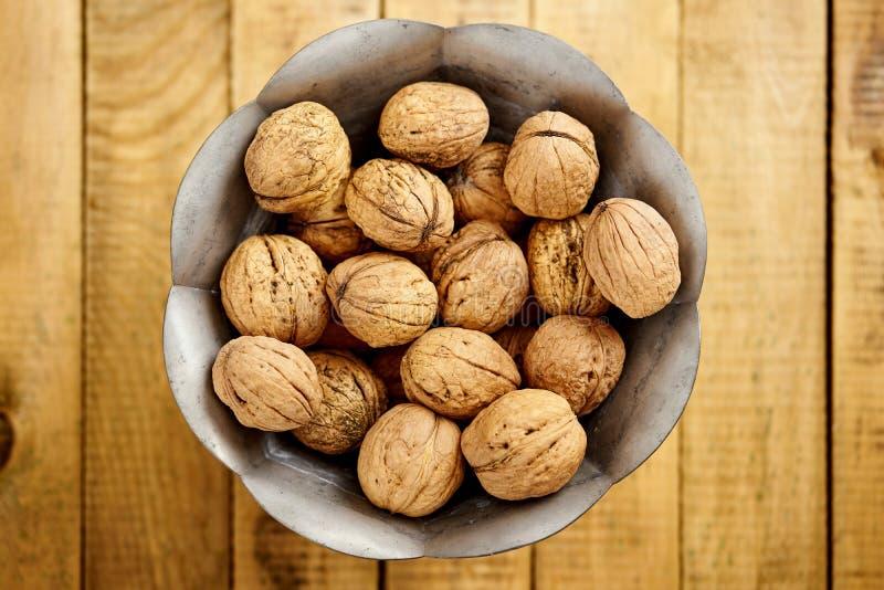 Cuenco por completo de nueces deliciosas y frescas en la tabla de madera fotos de archivo