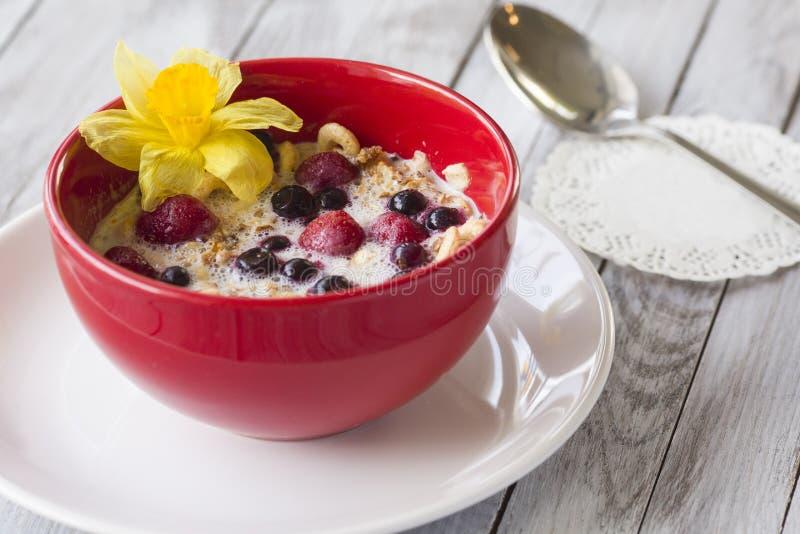 Cuenco rojo de cereal con las fresas con las bayas foto de archivo libre de regalías