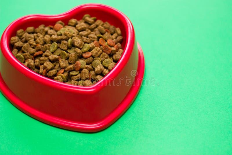 Cuenco rojo por completo de comida de perro multicolora imagenes de archivo