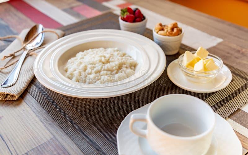 Cuenco sano de las gachas de avena del arroz del desayuno con las bayas y las nueces en la comida de la tabla, caliente y sana de imagen de archivo libre de regalías