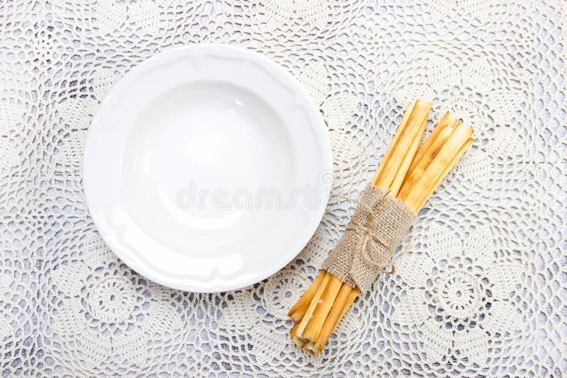 Cuenco vacío y breadsticks italianos tradicionales fotografía de archivo libre de regalías
