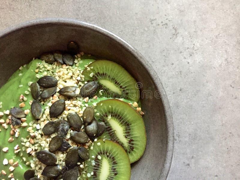 Cuenco verde del smoothie con los cañamones, el alforfón, las semillas de calabaza y el kiwi foto de archivo