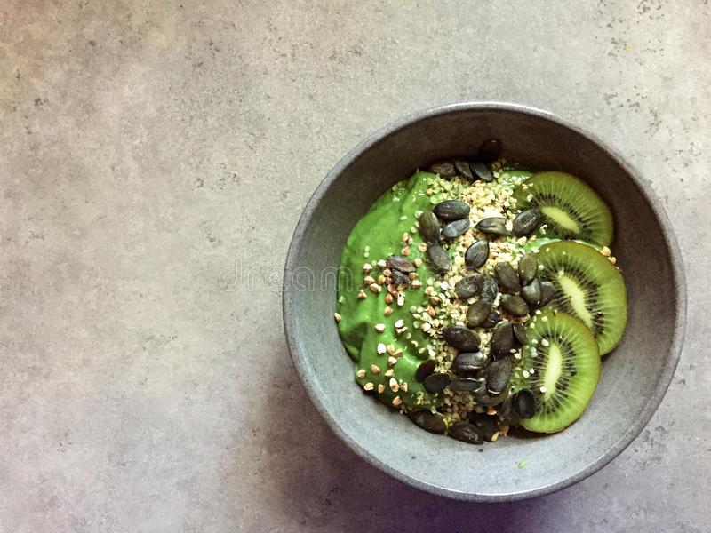Cuenco verde del smoothie con los cañamones, el alforfón, las semillas de calabaza y el kiwi imagen de archivo libre de regalías