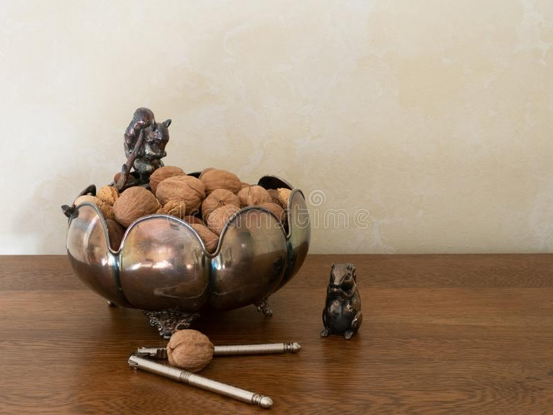 Cuenco y cascanueces de plata decorativos con las nueces mezcladas en Shell foto de archivo