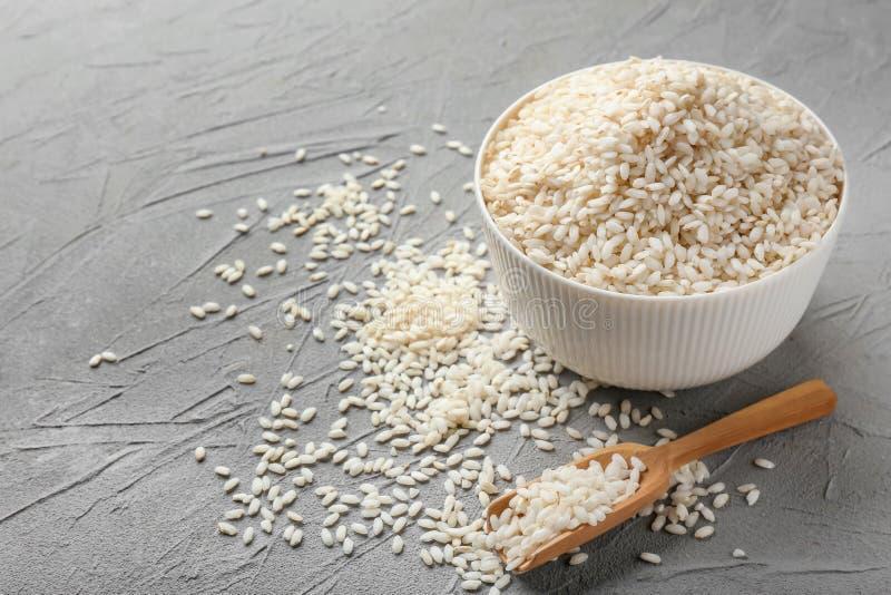 Cuenco y cucharada con arroz corto del grano en fondo ligero foto de archivo