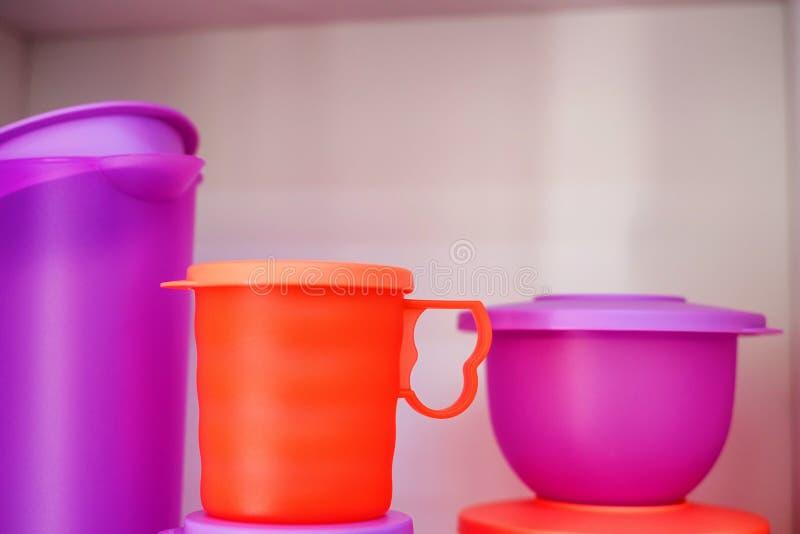 Cuenco y jarro plásticos coloridos del vajilla en estante imagenes de archivo