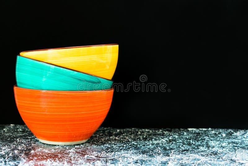 Cuencos coloreados brillantes de cerámica en un fondo negro Copie el espacio imagen de archivo libre de regalías
