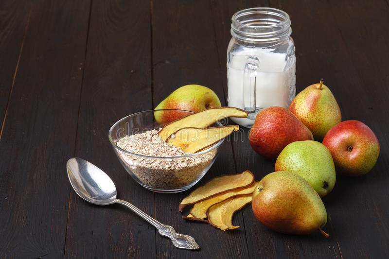 Cuencos con el desayuno y las peras sanos en una tabla de madera Homema fotografía de archivo libre de regalías