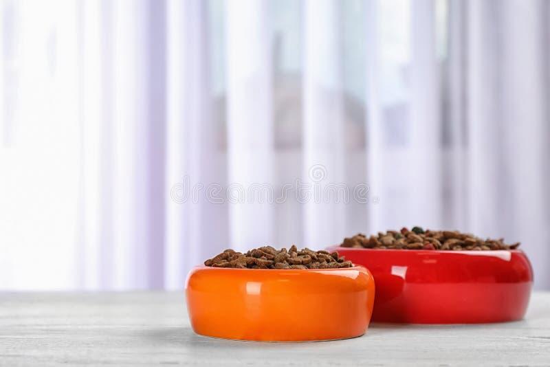 Cuencos con la comida para el gato y el perro en piso imagen de archivo libre de regalías