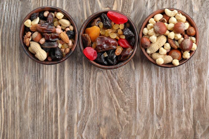 Cuencos con la mezcla de frutas, de bayas y de nueces secadas en el fondo de madera, visión superior imagen de archivo