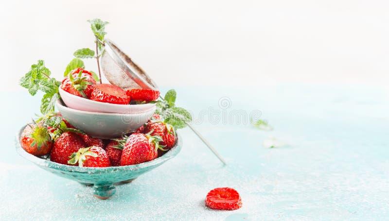 Cuencos con las fresas y el tamiz frescos del azúcar en fondo azul claro foto de archivo libre de regalías