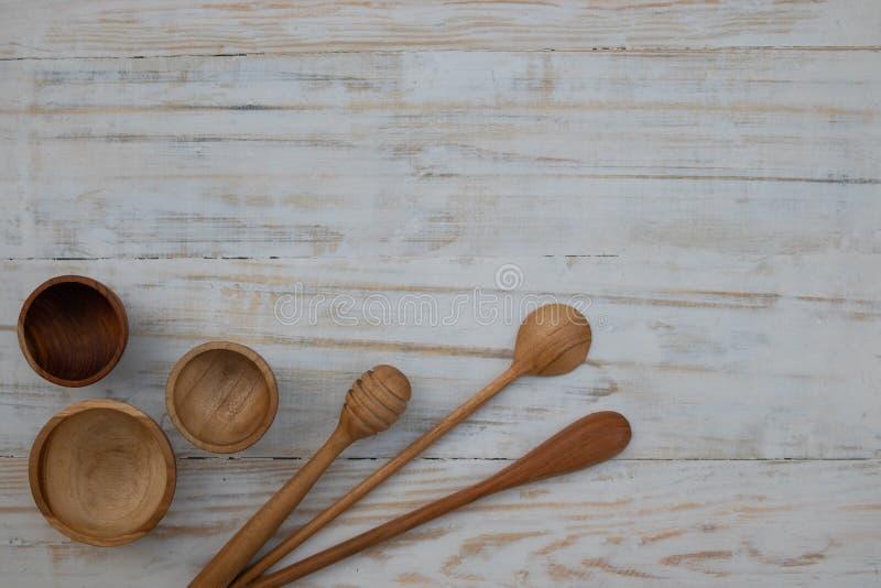 Cuencos, cucharas y palillo de madera respetuosos del medio ambiente de la miel en fondo de madera de la tabla Endecha plana del  fotos de archivo