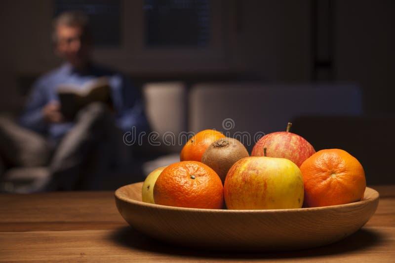 Cuencos de fruta en una mesa con un hombre leyendo en un sofá fotografía de archivo