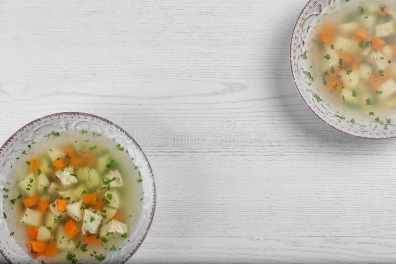 Cuencos de sopa hecha en casa fresca para curar gripe en fondo de madera fotos de archivo