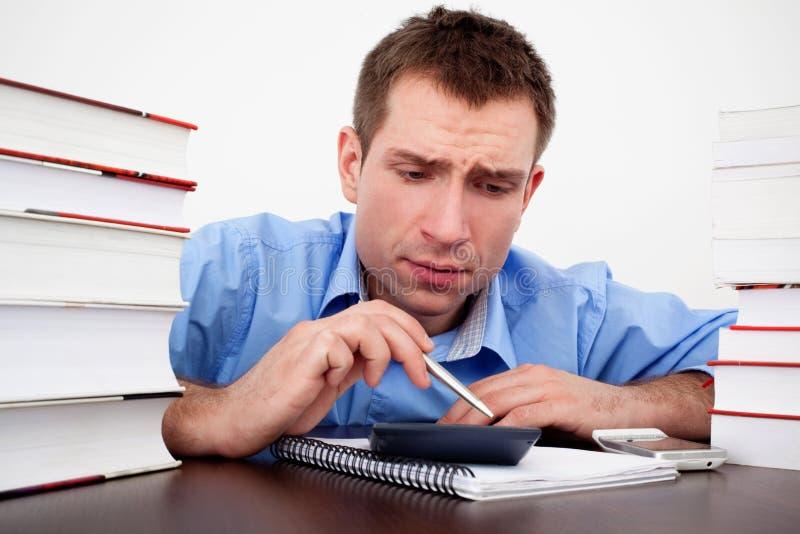 Cuenta asustada del estudiante masculino en la calculadora fotos de archivo