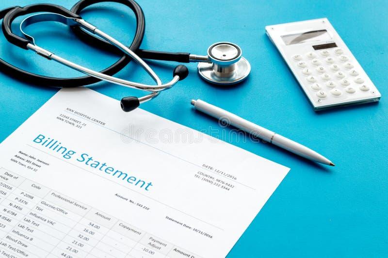 Cuenta, calculadora y phonendoscope del tratamiento médico en fondo azul foto de archivo