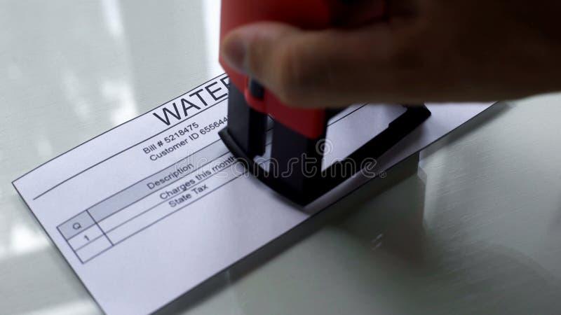 Cuenta de agua, mano que sella el sello en el documento, pago para los servicios, costos imagen de archivo libre de regalías