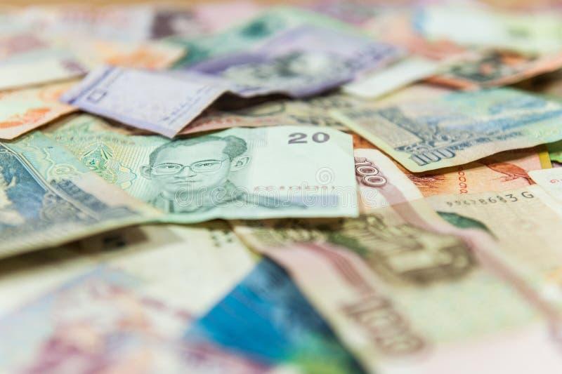 Cuenta de dinero del baht de Tailandia encima de diversos billetes de banco internacionales imágenes de archivo libres de regalías