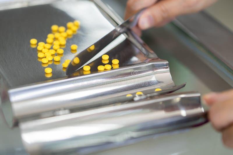 Cuenta de pequeñas píldoras amarillas en la píldora que cuenta la bandeja fotografía de archivo libre de regalías