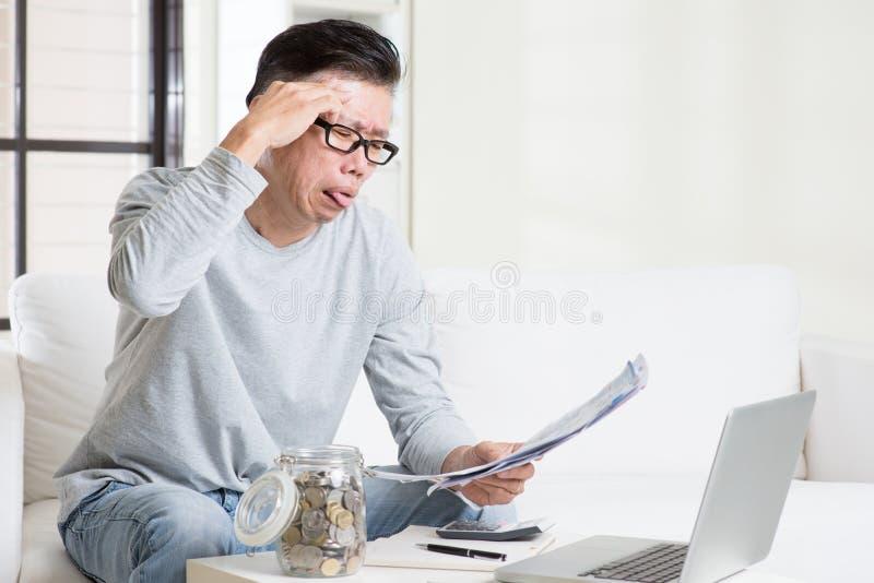 Cuenta que paga subrayada del hombre asiático maduro en casa foto de archivo libre de regalías