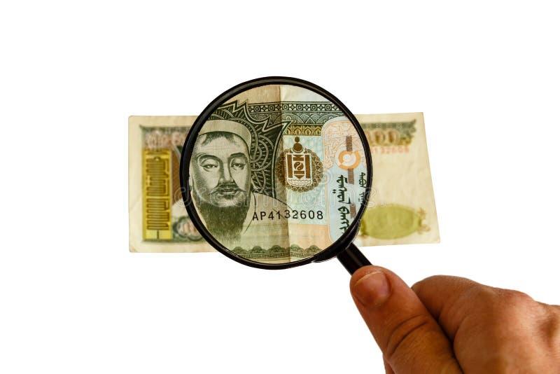 Cuenta y lupa mongoles de los tugriks a disposición fotografía de archivo