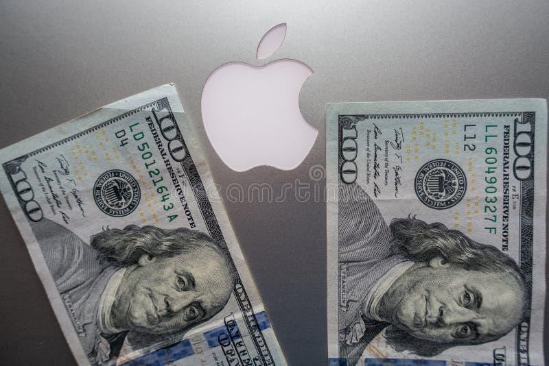 $100 cuentas contra el logotipo de Apple imagen de archivo libre de regalías