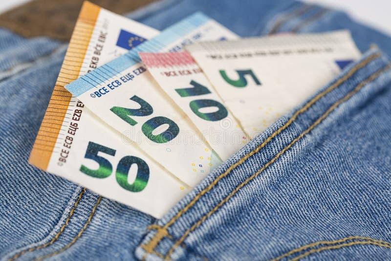 Cuentas de los billetes de banco de la moneda euro que pegan de la nada el bolsillo de los vaqueros foto de archivo libre de regalías