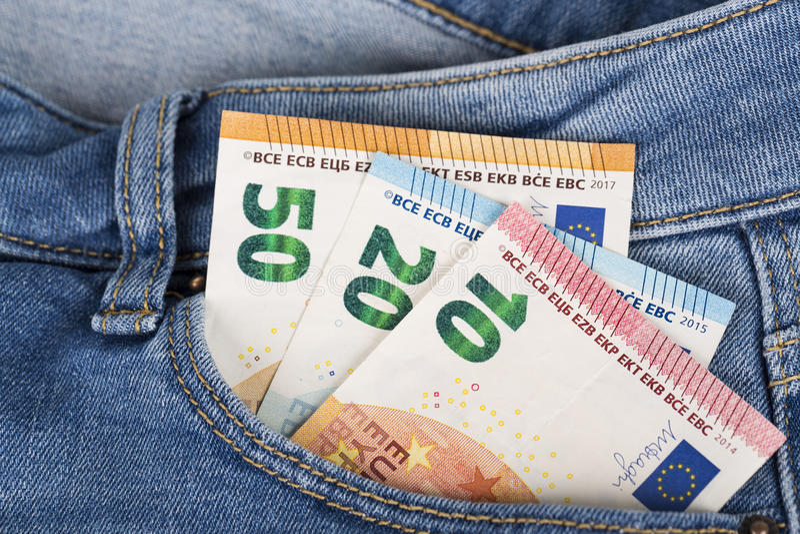 Cuentas de los billetes de banco de la moneda euro que pegan de la nada el bolsillo de los vaqueros imagenes de archivo