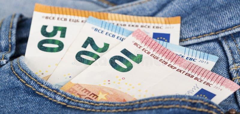Cuentas de los billetes de banco de la moneda euro que pegan de la nada el bolsillo de los vaqueros imagen de archivo libre de regalías