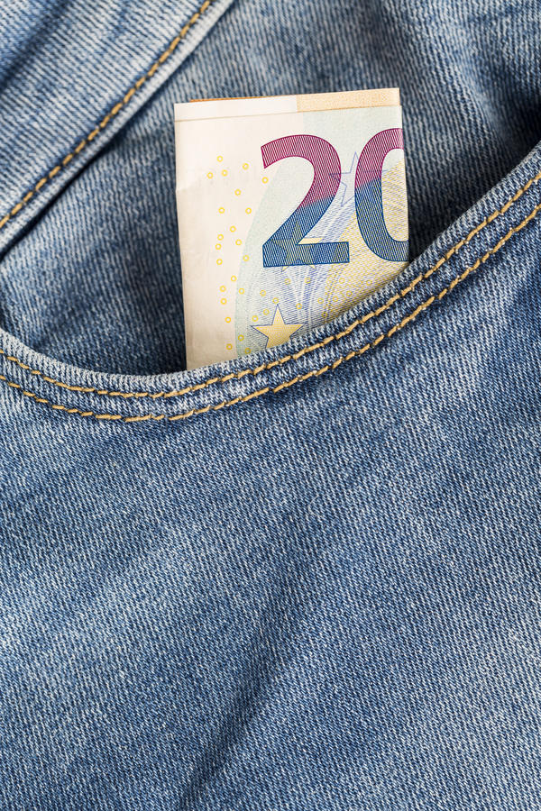 Cuentas de los billetes de banco de la moneda euro que pegan de la nada el bolsillo de los vaqueros imagen de archivo