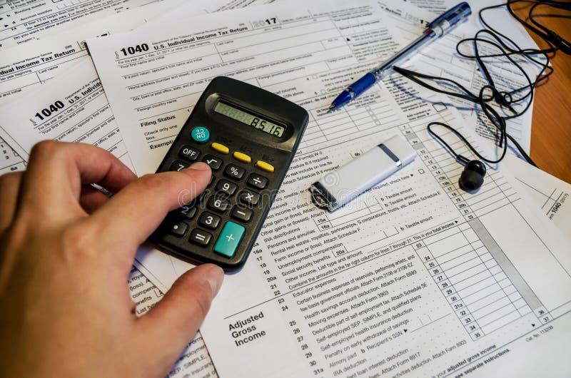 Cuentas femeninas de la mano en una calculadora Formas de impuesto 1040, memoria USB y pluma foto de archivo