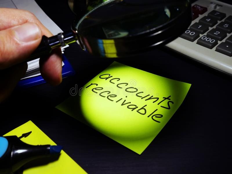 Cuentas por cobrar El contable mira a través de la lupa en un papel foto de archivo